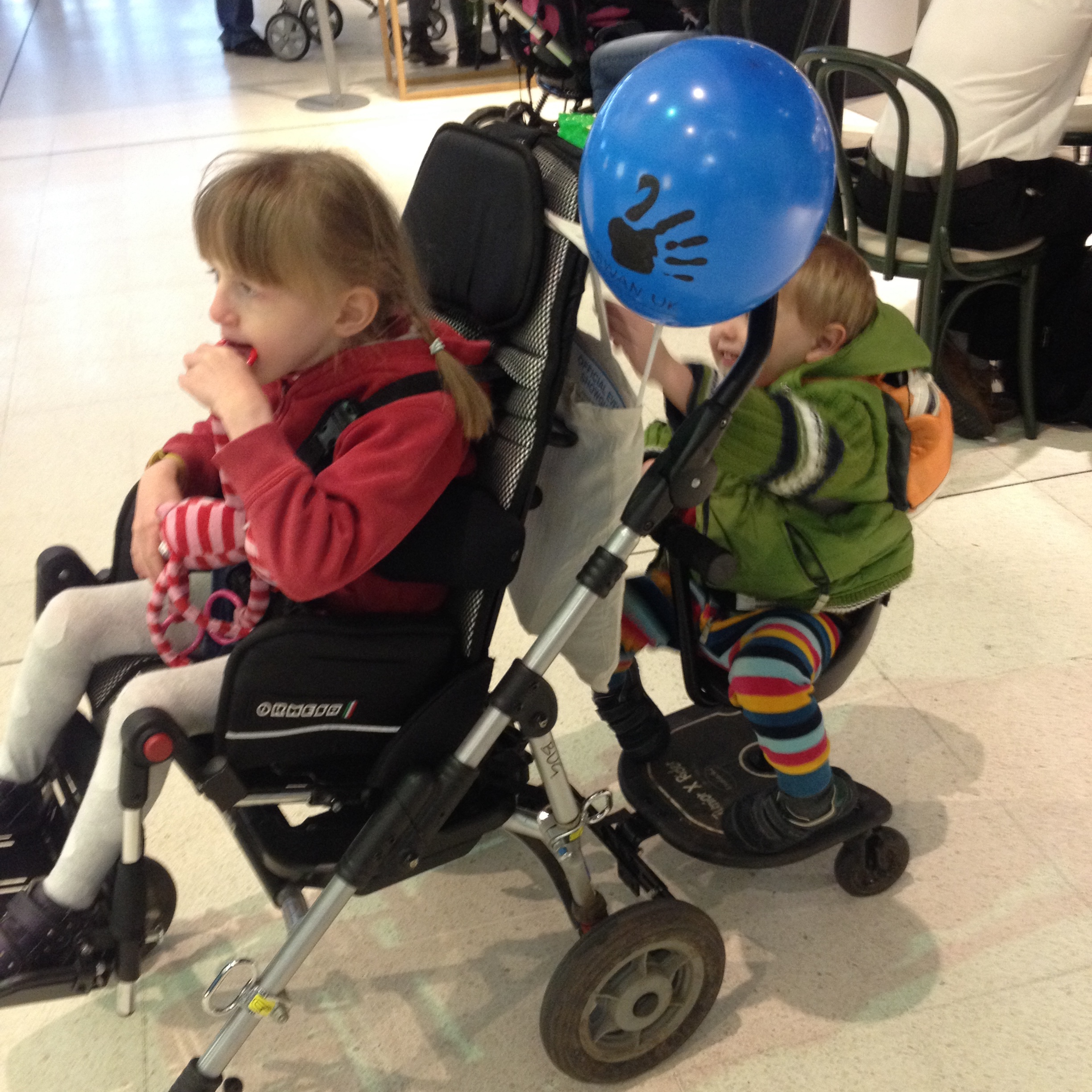 Wheelchair with buggy board and seat for sibling