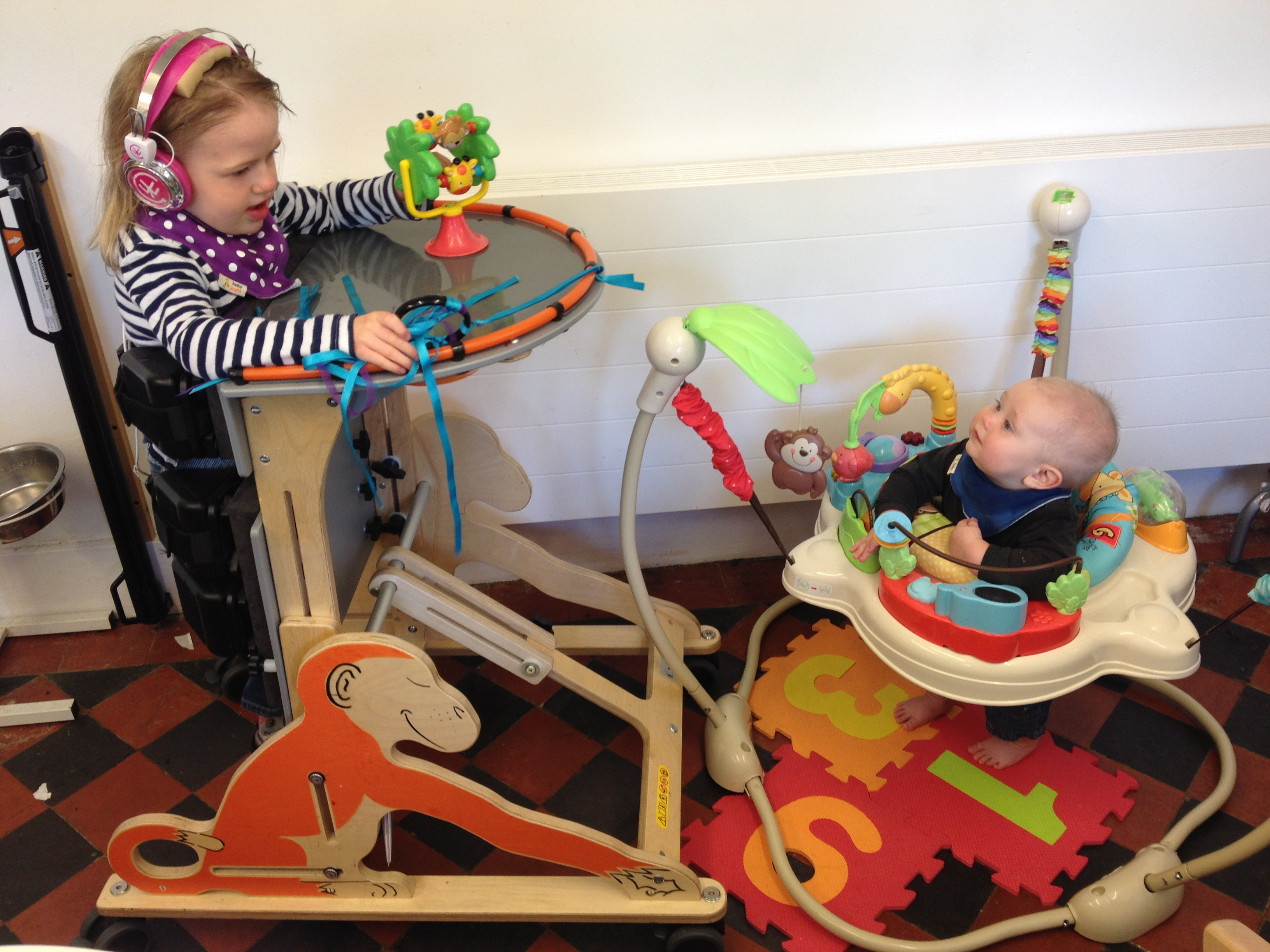 EJ in her standing frame facing her baby brother in a bouncer