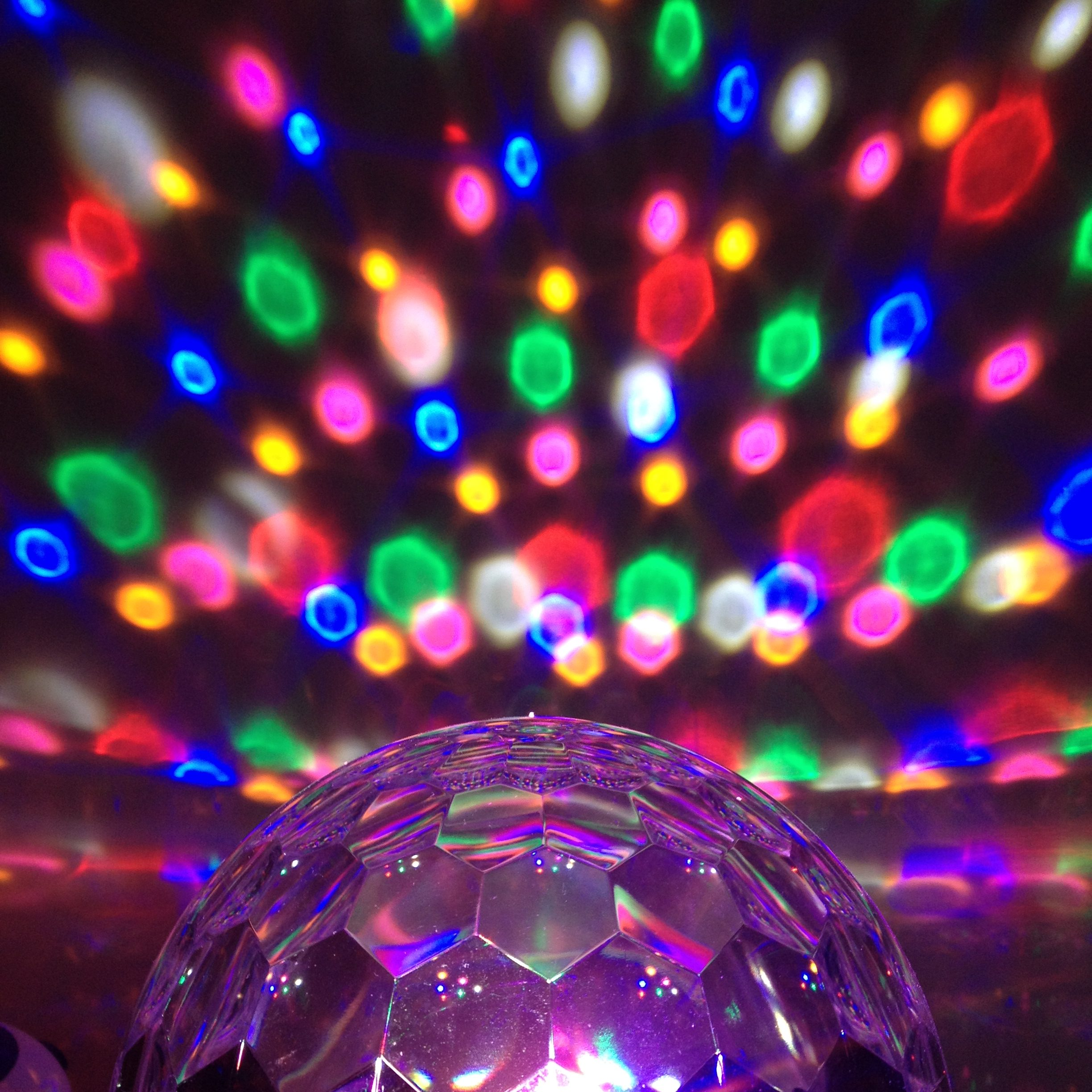 Disco ball light projecting coloured spots onto the wall
