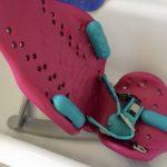 pink and turquoise splashy bath seat in white bath