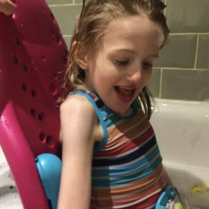 EJ sitting in the splash bath seat in the bath
