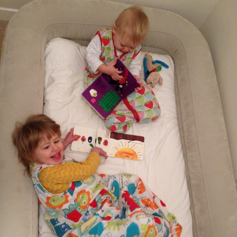 A younger J (3 years) and her brother (6 months) sitting in the Intex inflatable travel bed with their bedtime story books