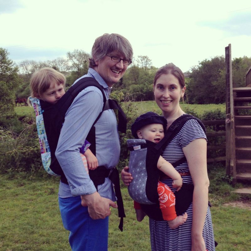Vaila & her husband on a country walk, each with a child in a carrier