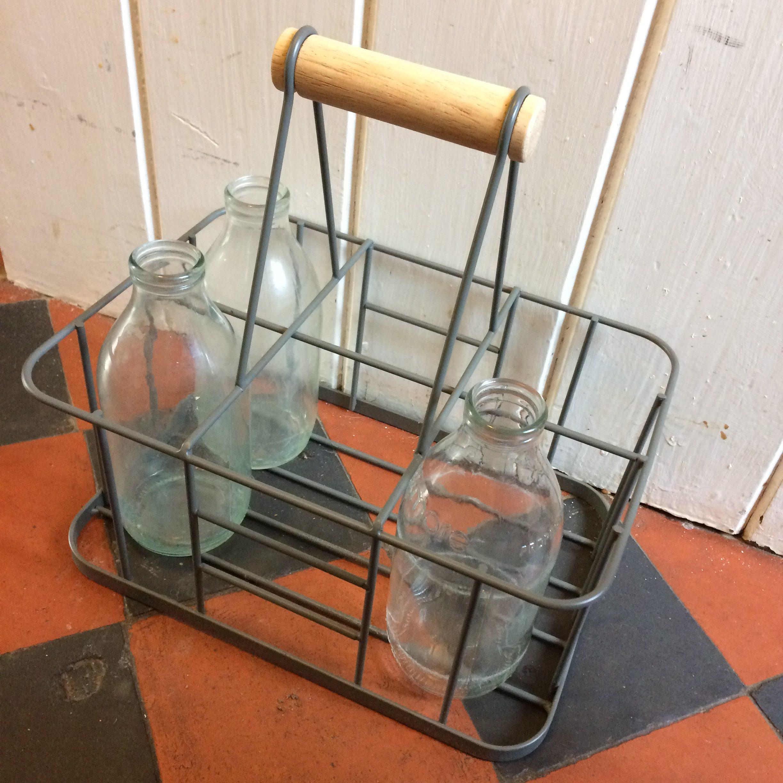 Empty glass milk bottles in a wire rack