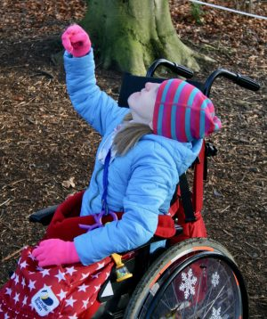 Photo of J in the woods, sitting in her wheelchair reaching up to the trees. Bundlebean blanket and snowflake spoke guard decorations are visible.