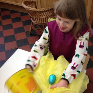 J sitting at a white table playing with some yellow tissue paper, wearing a deep red colour Care Designs tabard bib