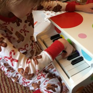 Close up of J in her christmas PJs, playing with a small wooden toy piano
