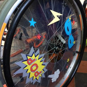 Photo of J's large rear wheelchair wheel with clear plastic spoke guard decorated with superhero style pop art stickers
