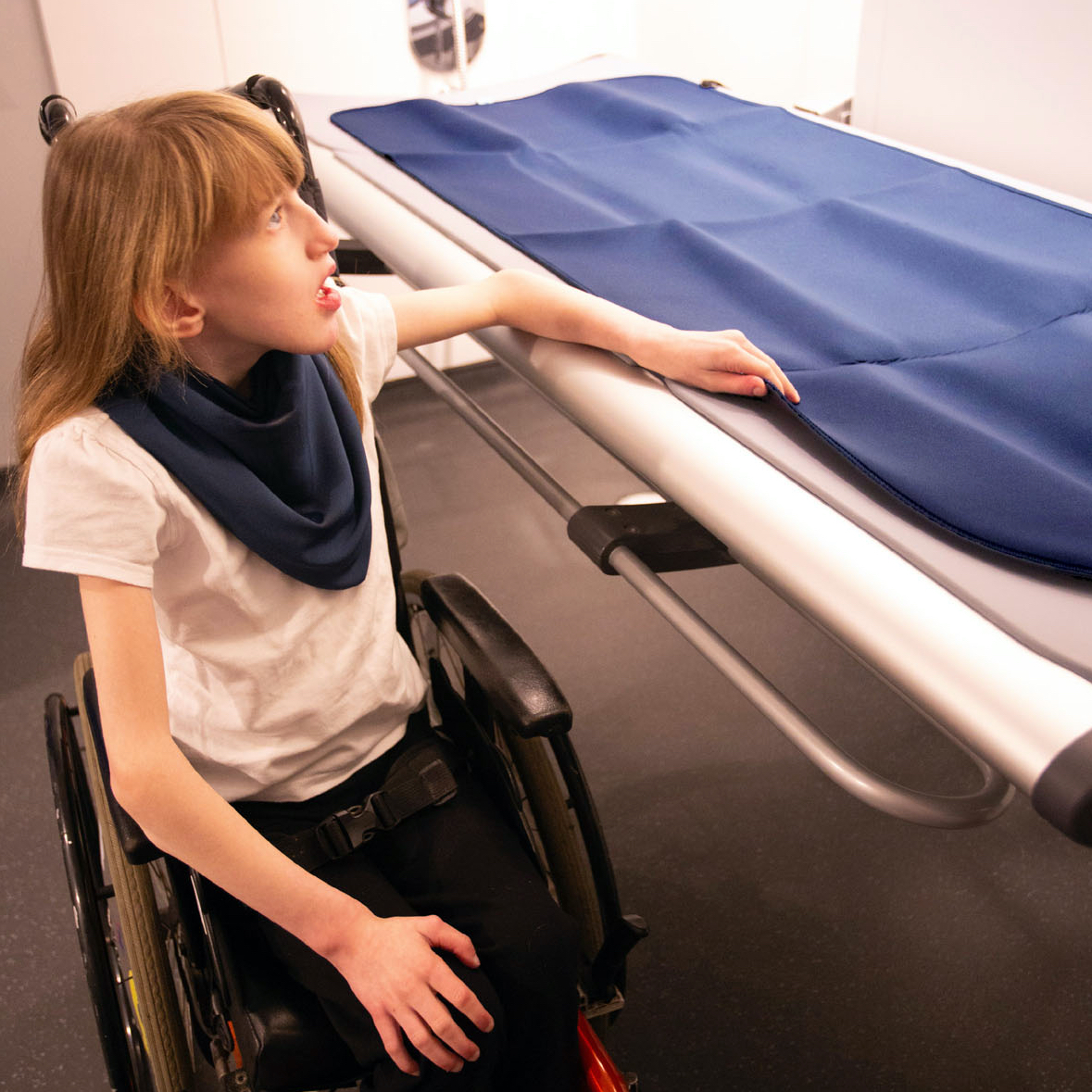 Young girl in a wheelchair next to a changing bench with a navy changing mat laid out