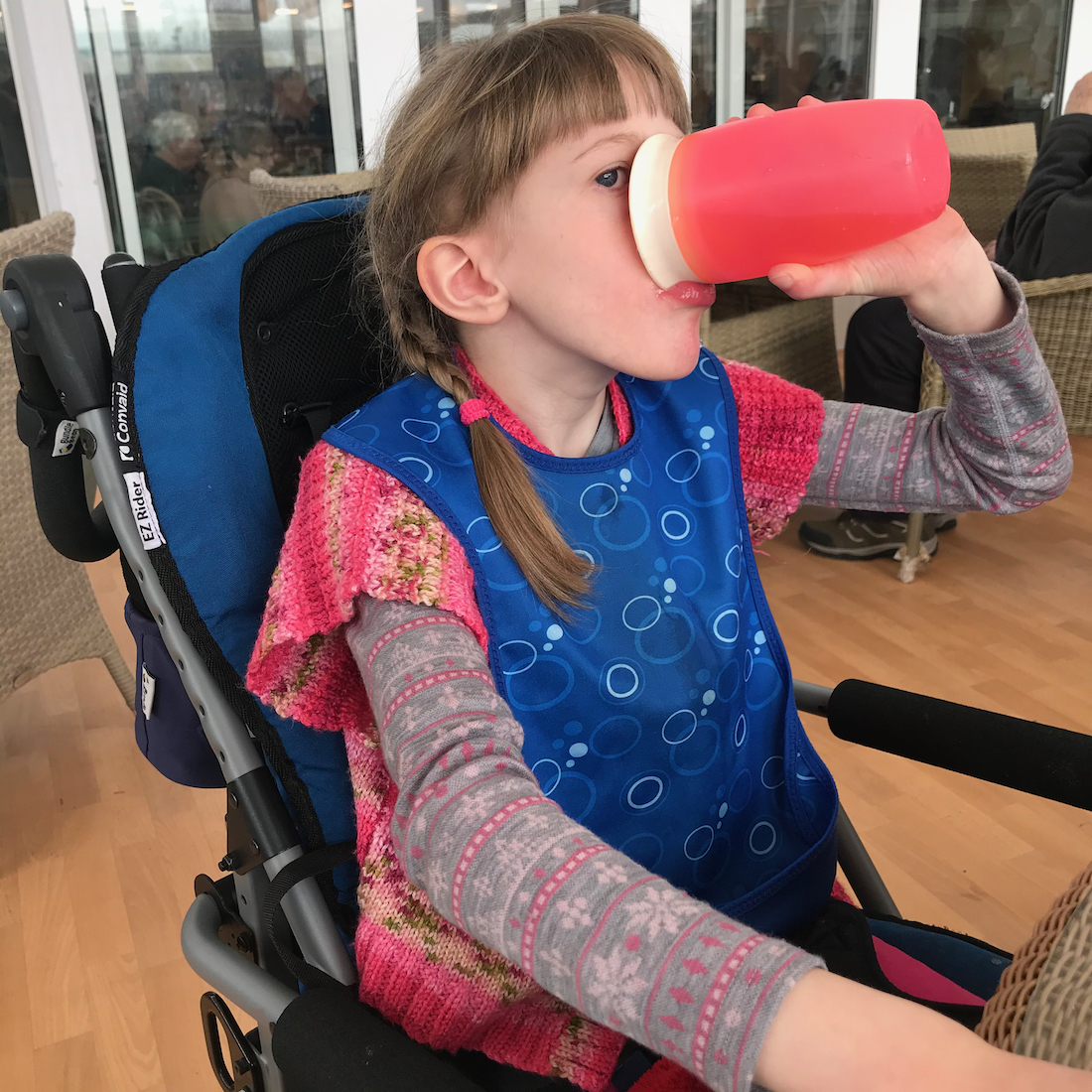 Young girl in a wheelchair wearing a blue tabard bib and drinking from a pink cup